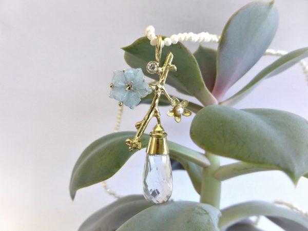 parelcollier met gouden bloesemtak hanger met diamant aquamarijn bergkristal